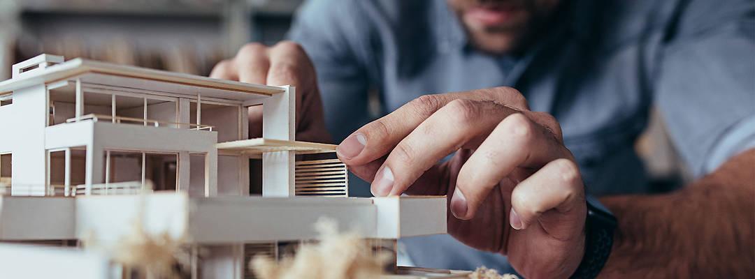 Architekt beim Erstellen eines Miniaturhauses